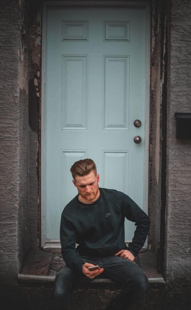 Мъж седнал пред входна врата
